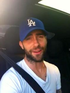 Adam Levine is wearing a baseball hat. And look at that breathtaking face! I'm done! Keep quiet while I stare at this