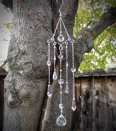 Enjoy the rainbows with this amazing crystal chandelier suncatcher! The pictures dont do it justice. Hang in front of a window and watch it sparkle! I have wire wrapped Swarovski crystal beads with crystal prisms, and hung them from chain to a hammered wire top. Accented with Swarovski