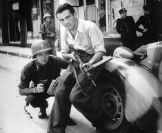 In France, an American officer and a French Resistance fighter are seen engaged in a street battle with German occupation forces during the days of liberation, August 1944, in an unknown city.