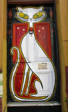 Door art. Cat painted door. Nice how they used a door knocker for the cat collar -  Valparaiso, Chile