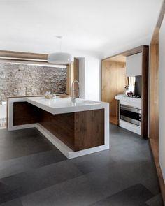 Cucina con muro di mattoni, cornici in legno massello e un'isola in bianco lucido