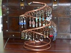Homemade earring tree made from copper pipe and wire. Drill holes along the pipe and thread short lengths of wire to create the loops to hold the earrings. Twist the wire ends and cut short.
