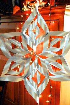 Step by step guide to making your own large paper snowflake for holiday decor. I used these for my daughter's wedding and hung them from the ceiling.