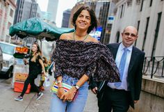 Leandra Medine in a Rosie Assoulin top,  with an Edie Parker bag and an Annelise Michelson earring