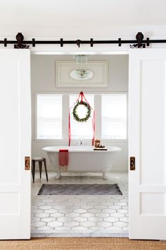 "The bathroom's barn doors are the result of a successful junking expedition—right under the Gearharts' roof! The striking pair was discovered during the kitchen renovation. ""We opened up the wall, and there they were, still hanging on their beautiful original hardware,"" Jennaea says. Spruced up with—yep—more white paint, they frame the bath's 8"" x 8"" cement hexagon tiles (sabinehill.com) and clawfoot tub. Bright idea: Hang a mirror high! An antique mirror above the windows keeps the vaulted…"