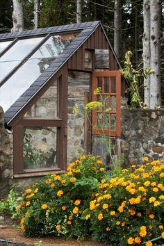 Stone house, stone walls around the garden and solar greenhouse at Helen and Scott Nearing's Good Life Center, Maine