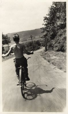 JIM      RIDING    HIS    BICYCLE    DOWN    THE    DIRT    ROAD    PLAYING