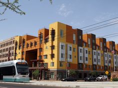 """A Metro Light Rail train rolls by the Devine Legacy apartment building along Central Avenue in Phoenix. The energy-efficient complex includes 65 """"urban style"""" apartments."""