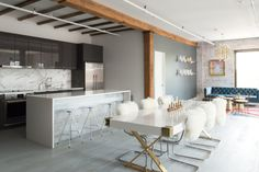 From the open, blank box of the loft, Allison had to stake out the kitchen and dining area, a formal sitting area, and a living space. A clever layout made everything fit, without making it seem overcrowded.