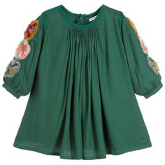 Made by Chloé, this beautiful emerald green dress embodies the elegance and supreme femininity of this prestigious brand, and mirrors the womenswear designs with its exquisite detailing. Gathered at the neck and gently flared, it is decorated with fluffy appliqués and is neatly trimmed with braiding. The softness of the viscose twill fabric ensures fluidity and drape, and the back of the dress fastens with a zip and single button.