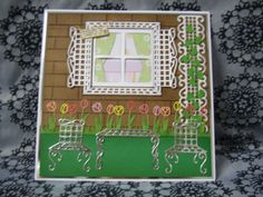 Tattered Lace Country Garden Collection, Outdoors garden scene card using the Tattered Lace tulips die, multi cuts of the bench die for window frame, shutters and garden furniture, Eltham border die for the trellis and oriental ivy die for foliage. Background embossed brick pattern done using the Hougie board then distress ink.