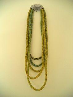 Collar realizado con diferentes tiras tejidas con tricotín