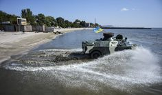 Servicemen of the Shakhtarsk battalion drive their APC towards the water line during training session on a beach in Mariupol on September 15, 2014. (ALEKSEY CHERNYSHEV/AFP/Getty Images)
