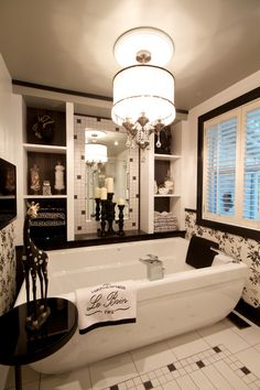 LOVE this glamorous, black and white bathroom!! I need a free standing tub. and that light fixture above it!!
