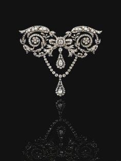 Diamond devant de corsage, circa 1905 -  Of foliate, scroll and bow design suspending  two pendants, set with cushion-shaped, circular-cut  and rose diamonds
