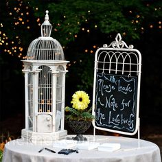A chalkboard directed guests to drop their well-wishes for the couple into a tall antique bird cage.