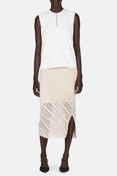 A pristine sense of understatement allows focus to fall on the cut of this bright white Altuzarra top, a wear-with-everything staple made modern with thoughtful details like a sharp split neck and a layered hem. The meeting of wardrobe essential and elevated allure is unmistakably Altuzarra, and one that is woven throughout the designer's pre-fall 2016 collection by pieces like this fluid blouse.