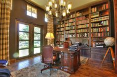 Dark wood book shelves, cabinets, table, chair & floor. Even the other side of the wall along with door & window frames is painted with dark brown.