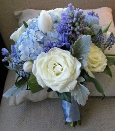Blue and White flower bouquet with satin ribbon on the stem. Site with winter wedding pics..we aren't doing a winter theme but we are using blues and silver now so these are helpful pics