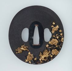"Goto Mitsuhiro (1797-1845) -  Goto School Tsuba, with Inlaid Designs of Shishi and Peonies. Shakudo, Gold, Copper, Sekigane, with Nanako-ji Surface and Iroe Takazogan Decorative Technique. Circa Early to Mid-19th Century. 3-1/4"" x 3-1/16"" x 1/2"" (8.2cm x 7.8cm x 1.2cm)."