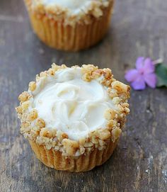 Carrot cake cupcake with pineapple flavored cream cheese in the center, cream cheese frosting and chopped walnuts.