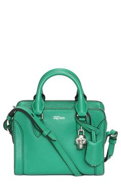 Chic emerald green Alexander McQueen duffel bag with a signature skull-shaped padlock.