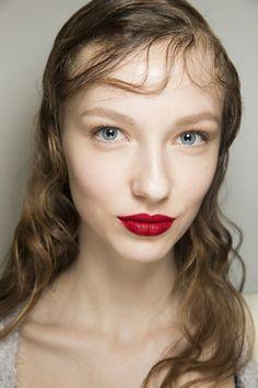 Een natural glow op het gezicht, appeltjesrode lippen en gekruld haar met een wet look bij Prada