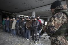 An armed man of the separatist self-proclaimed Donetsk People's Republic army (R) guards Ukrainian war prisoners in the damaged Donetsk airport , February 26, 2015. REUTERS/Baz Ratner