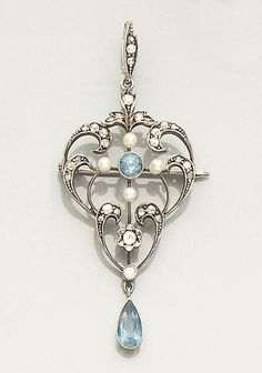 An early 20th century aquamarine, diamond and seed pearl brooch/pendant  The openwork cartouche-shaped mount set with old brilliant and rose-cut diamonds, a central circular-cut aquamarine and four seed pearl accents, the whole suspending a pear-shaped aquamarine drop, length 5.7cm