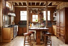Designer Mick De Giulio transformed an old Illinois Barn into this inspired kitchen. He designed the pot rack to resemble a wagon wheel, cut in half. Stools by Ebanista covered in Holly Hunt leather. The floor is made from reclaimed barn planks.   - HouseBeautiful.com