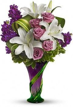 Indulge Her Bouquet  Go all out for Mom with luscious lilies and roses in a spectacular hand-blown art-glass vase sculpted with a stylish climbing vine motif. It's a breathtaking gift she'll love forever – and love showing to her friends.        * The stunning bouquet includes white lilies, lavender roses and purple stock accented with assorted greenery.