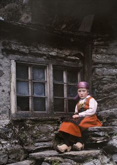 A young girl sits on stone stairs that lead up to her house. Southern Alps, Italy. Kulturwächter