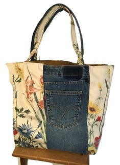 "This one-of-a-kind bag is made with up-cycled decorator and apparel fabrics. It is about 17"" wide, and 15"" tall. The stunning floral spring print combines with denim. It has one large patch pocket in the goldenrod burlap lining, and two jeans pockets on the outside of the bag. There is a removable covered plastic insert in the bottom of the bag. This is a great bag for crafts, books, knitting, shopping, and more!"