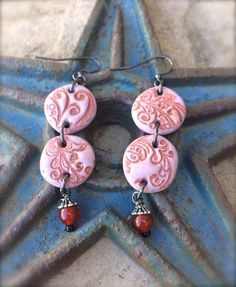 lavender colored clay circles with reddish-brown imprint have a genuine round carnelian bead dangling from the bottom. #hippsieloveshop #etsy