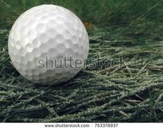 Golf ball lies on the grass, which is covered with white ice crystals.