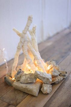 pretend fire. Make a ring of river rocks. Cut thin logs and glue in teepee shape. Use a string of christmas lights and coloured celophane.
