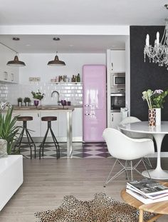Kitchen with a pink fridge, subway tile backsplash, and a chandelier.