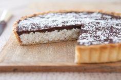 Recette de Tarte choco coco, Une tarte garnie d'un mélange à base de noix de coco râpée, de crème et de sucre, cuite au four puis nappée de chocolat noir : un vrai délice !