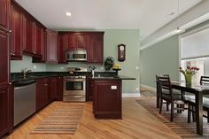 Light Sage Green Paint Colors In Kitchen With Dark Mahogany Cabinets With Black Countertops With Pendant Lighting And Laminate Floor How to Select Right Paint Colors for Kitchen with Dark Cabinetry, Marble kitchen island colors, Affordable modern kitchen cabinets