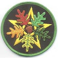 "Oak Leaf Pentagram Oak Leaf Pentagram       Sew this beautifully embroidered cloth patch to favorite clothing, ritual wear, or accessories. This patch displays an intertwined gold pentagram with 5 oak leaves spread atop it, and an acorn in the center, with a bright green border. It measures 3"" diameter.  ..."