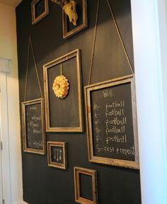 mur de cadres en bois rustiques, formats divers, couleur mur noire, decoration fleur en papier et trophée, grand tableau noir