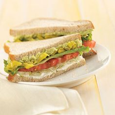 Summer Veggie Sandwich  4 ounces cream cheese, softened  8 slices whole wheat bread  1 small cucumber, sliced  1/2 cup alfalfa sprouts  2 teaspoons olive oil  2 teaspoons red wine vinegar  1 large tomato, sliced  4 lettuce leaves  3/4 cup sliced pepperoncini  1 medium ripe avocado, peeled and mashed