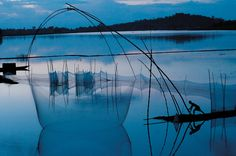 At twilight on floodwaters from the Brahmaputra River, a fisherman maneuvers a net on bamboo poles; EPA/Corbis