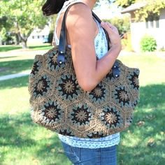 Hand-crocheted into a fashionable sunburst pattern, this yarn handbag has a look all its own. Leather shoulder straps and a zipper closure top this handmade bag from Thailand.
