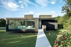Black Modern House Consisting of Five Modules Clustered Around a Central Courtyard