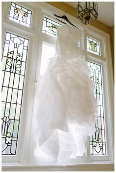 Wedding dress hanging in stained glass window, Kelly Adrienne Photography