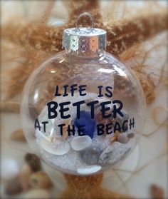 "Clear christmas glass ball filled with shells and sand and saying ""life is good at the beach"""