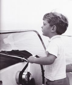 John Jr. plays at being skipper, late August 1963. He was intelligent and exuberant, endlessly fascinated by the world around him, particularly all things mechanical.