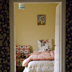 Bedroom: Modern Retro: Wallpapered floral wall with yellow wall and floral bedlinen