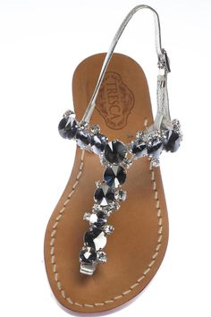 Amalia is an Italian sandal that features clear, silver and black crystals adorning a silver Italian leather adjustable strap. Amalia comes in the 2 heel heights pictured and can be made to accommodate a wide width. Our soles are European sizes made in Italy. They are made from Italian leather with a wrapped, wooden heel. Please consult the size guide. If you're a half size, size up. All of our Italian sandals are handmade to order by our cobbler in store. We keep true to the Capri sandal by…
